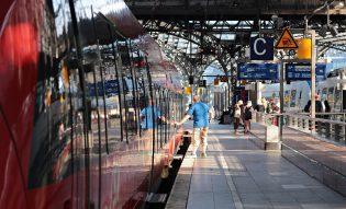 Vu en prolongement d'un train rouge à quai - des personnes attendent au soleil - un homme chauve vêtu d'un bermuda et d'un polo bleu ouvre la porte du train