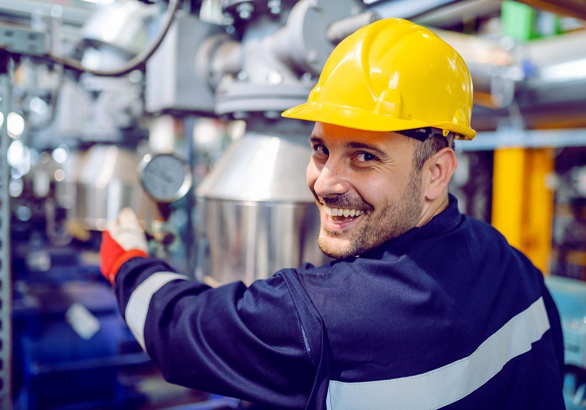 Ouvrier souriant avec casque jaune de sécurité