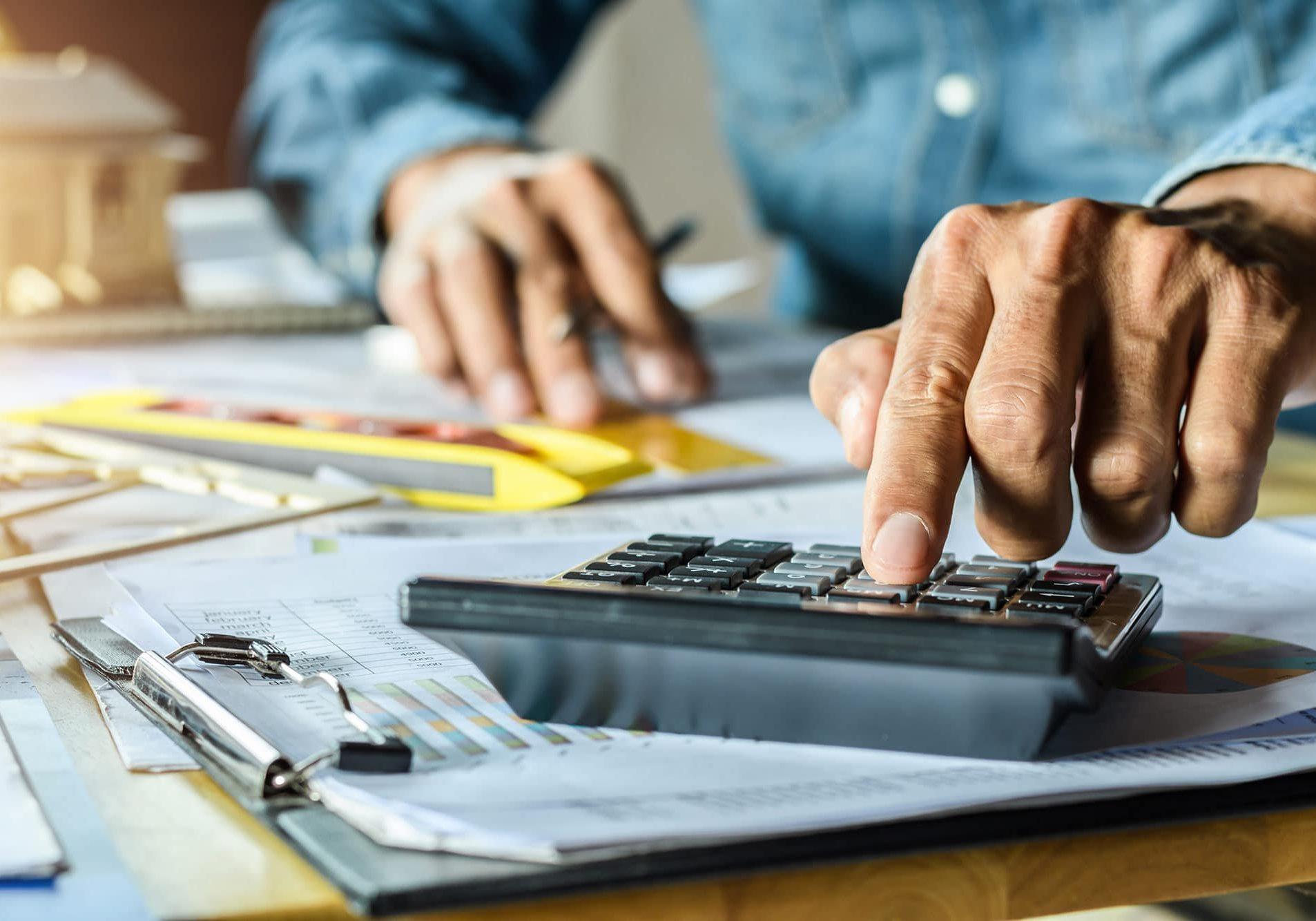 Plan sur les mains d'un homme qui travaille avec une calculatrice, documents et outils de mesures